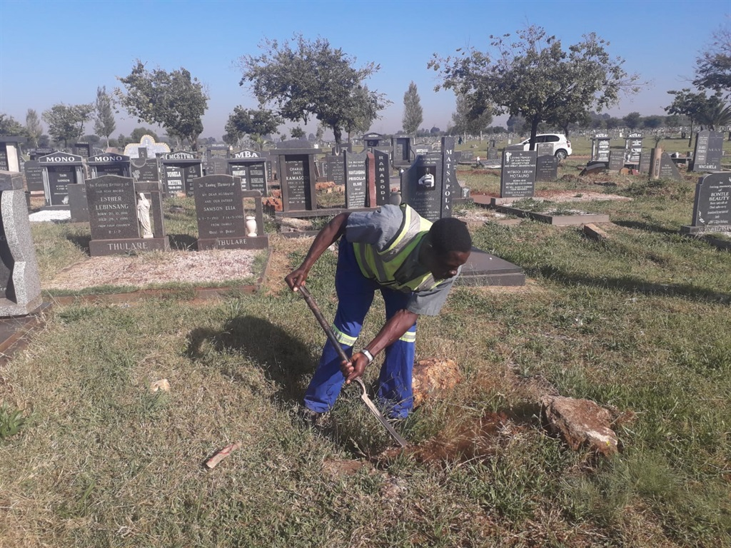 Duncan Nemudzivhadi cleaning a grave in the Avalon Cemetery.