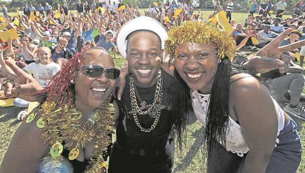 Vicky Khoza (left), her son Miso and daughter Amanda, are backdropped by a crowd of pupils supporting Miso during Pelham Senior Primary's Shine fundraiser to raise money for Miso's medical bills.
