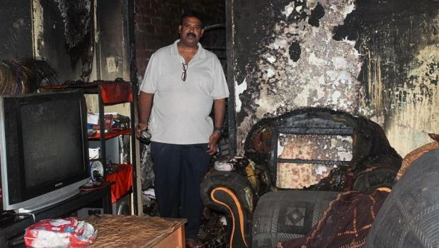 Mano Pillay stands in the burnt Bombay Road house. Pillay was one of the first people who saw the fire and alerted emergency services.