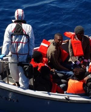 Rescued migrants sit in a Italian Navy's boat in the Sicily channel. ((Italian Navy, via AP)