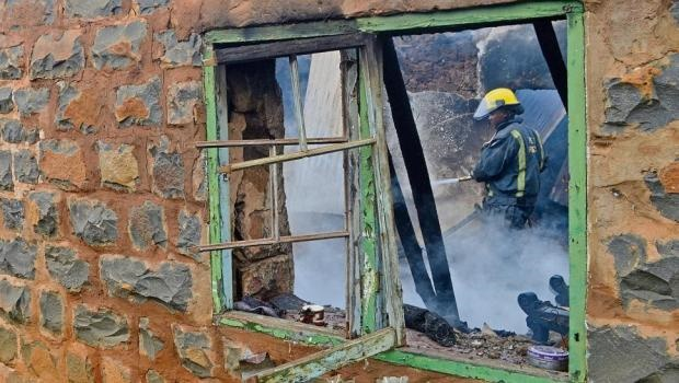 A member of the Pietermaritzburg fire department extinguishes the flames after a fire broke out in Emvundlweni village outside Edendale, killing a child.