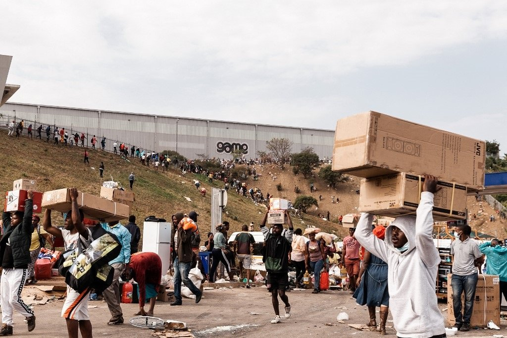 Looters carry goods from the Game Warehouse in Durban.