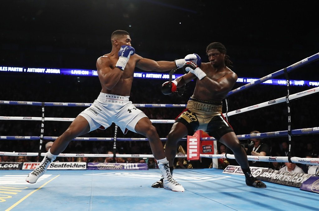 Anthony Joshua puts Charles Martin at bay with a left hook during their IBF heavyweight title fight at O2 Arena in London last Saturday. Joshua won by a second round knockout and he is being touted as Britain top-class world champ Picture: Reuters / Andrew Couldridge Livepic