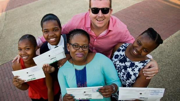 Sobantu Secondary School pupils (from left) Fezeka Bhengu, Thobeka Shange, Thandeka Sibiya (teacher) and Nokubonga Xaba with Save Hyper regional manager Garth Lloyd holding up their plane tickets for their trip to Dubai.
