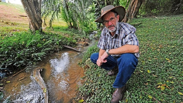 Johan von Reiche next to a river of drinking water that has flowed for years through Oak Park from a burst pipe near the Ferncliffe Reservoir.