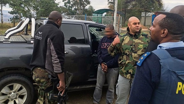 One of the four men arrested on Wednesday surrounded by Magma Security and police officers in the Creighton area.