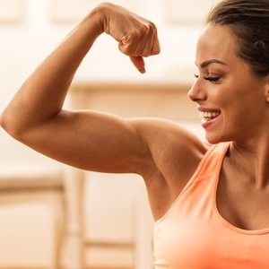 Profile of proud young woman showing off her arm m
