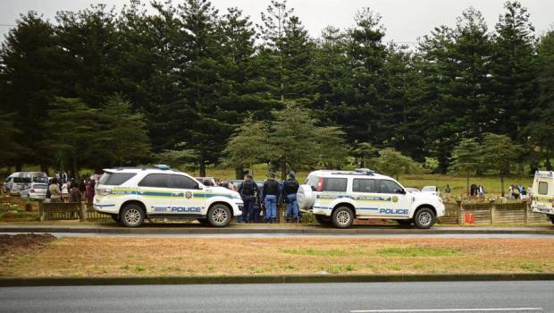 Heavily armed police keep a watchful eye on friends and family of notorious gang leader Ian Williams, who was laid to rest at the Mountain Rise Cemetery.