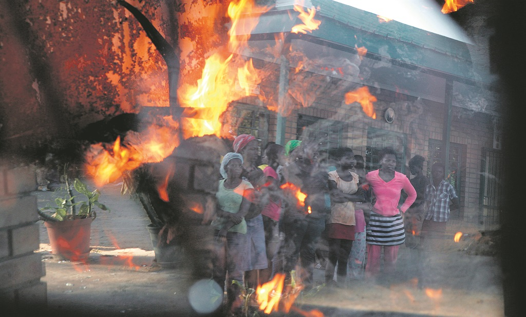 People watch as the Mariadza Inclusive School burns in Limpopo. Schools in the area were burnt down last week by disgruntled residents protesting against municipal demarcation  PHOTO: Sandile Ndlovu / Gallo Images