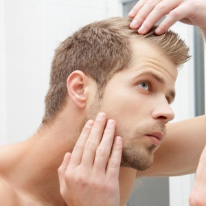 young man checks for receding hairline in mirror