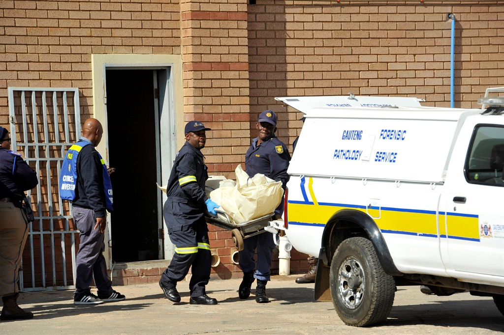 Police officers load the body of a man killed during the unrest in Tshwane on June 22 2016.