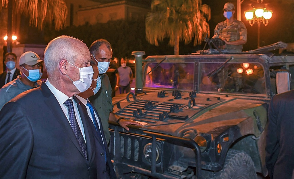 Tunisian President Kais Saied walking past a military vehicle, after he ousted the prime minister and ordered parliament closed for 30 days.