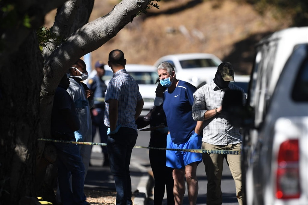 William Booth (in blue shorts) speaks with police officials outside his Higgovale home shortly after the attempt on his life on the morning of 9 April. Photo - Jaco Marais