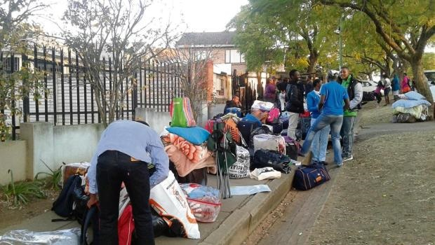 Stranded pupils standing outside the property they rented in Alexander Road on Wednesday afternoon.