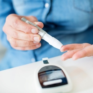 diabetes patient uses blood glucose monitor