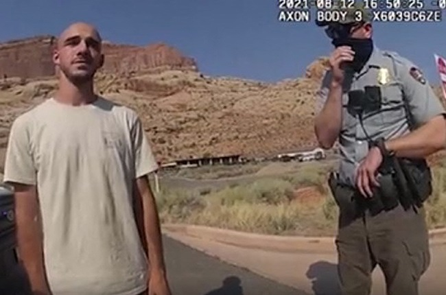 This 12 August 2021, still image from a police bodycam released by the Moab City Police Department in Utah, shows Brian Laundrie (L) speaking with police.