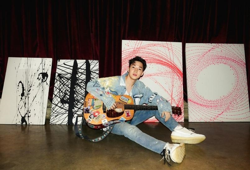 Henry Lau poses with his artworks in his studio in