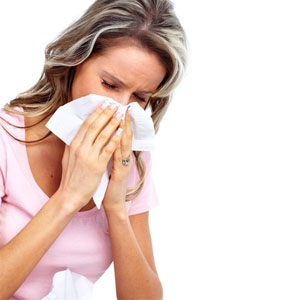 Woman with hay fever blows her nose