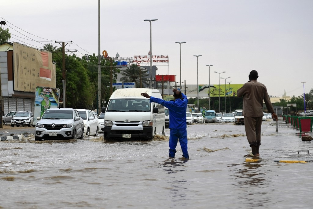 Cars drive along a flooded street in Khartoum after torrential rain fell on the Sudanese capital, almost paralising traffic.