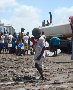 A child crosses through mud as people receive rations of water at the UN compound in the Tomping area in Juba. (AFP)