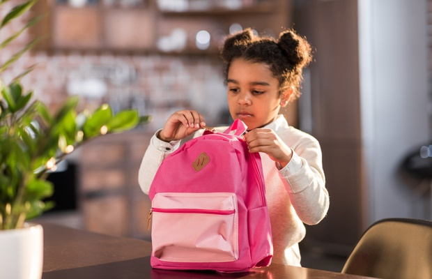 girl packing pink backpack