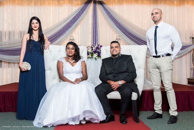 The bridal couple, posing with friends and family