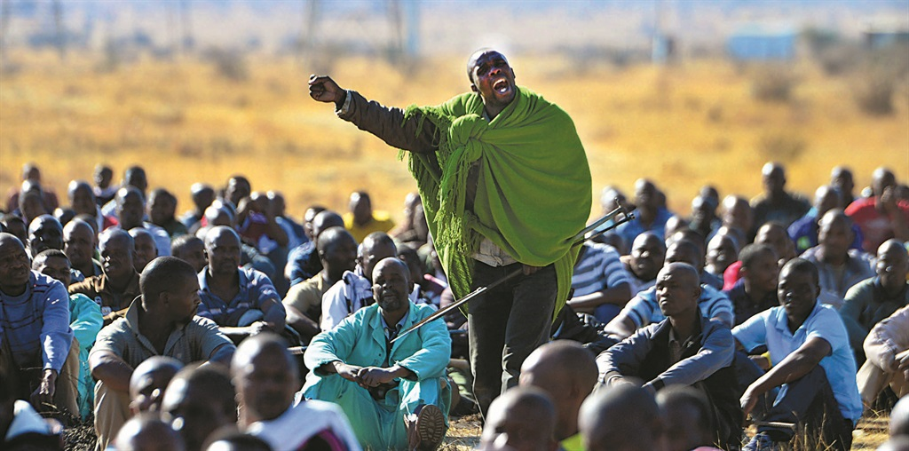 EXHORTING STRIKERS Mgcineni Noki, also known as the man in green blanket, rallies the miners at Marikana ahead of their encounter with police that left more than 35 miners dead, shot by the police. Picture:Leon Sadiki.