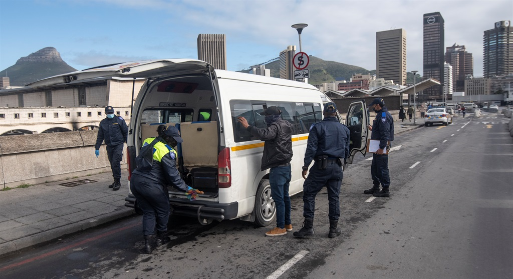 Police search a taxi in Cape Town after an alleged shooting incident involving rival taxi drivers. Photo: Gallo Images/Brenton Geach