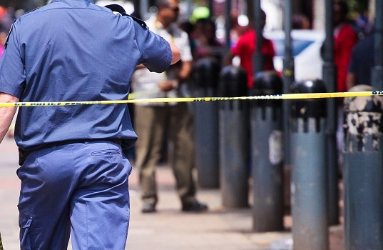 Police officer behind police tape at a crime scene.