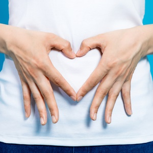 Woman holding hands in a heart over her stomach