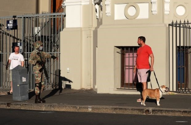 A member of the South African Defence Force talks to man taking his dog for a walk.