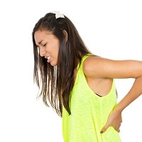 Girl with juvenile arthritis holds her back after