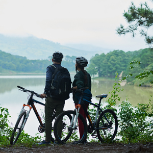 Couple with their bicycles looking at a lake