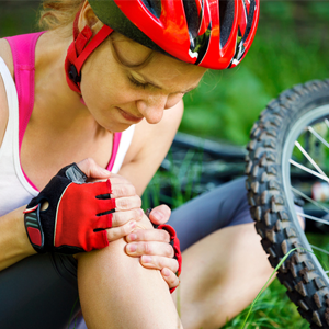 Woman cyclist with an injured knee