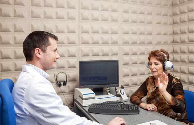 Audiologist testing a woman's hearing