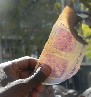 A protester opposed to the introduction of bond notes burns a Zim dollar note. (Memory Mataranyika)