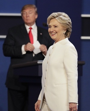 Democratic presidential nominee Hillary Clinton walks toward the audience as Republican presidential nominee Donald Trump stands behind his podium after the third presidential debate in Las Vegas. (John Locher, AFP)