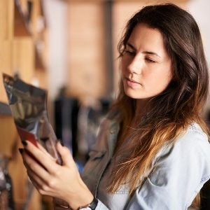 woman checks food label on packaging for allergens
