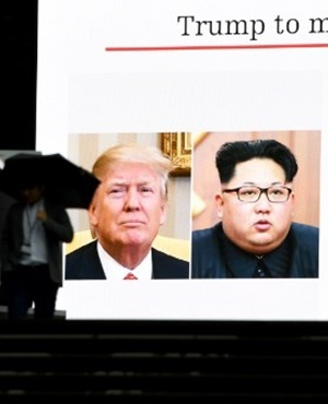 A pedestrian walks in front of a huge screen flashing a news report relating to US President Donald Trump and North Korean leader Kim Jong agreeing to meet for talks in Tokyo, Japan. (Toshifumi Kitamura, AFP)