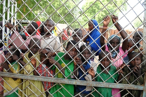 This photo taken on June 30, 2016 shows displaced children watching from behind a fence, as malnurished and sick kids are being taken away in an ambulance for treatment in Bama's camp for internally displaced people (IDP), in Borno State, northeastern Nigeria. (AFP)