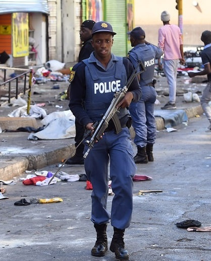 A police officer walks through the Johannesburg city centre on September 2 after shops were set alight and goods looted. (Felix Dlangamandla, file)
