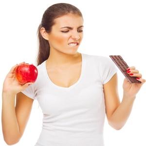 woman choosing between chocolate and apple