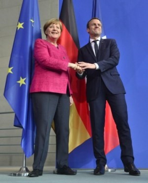 German Chancellor Angela Merkel and French President Emmanuel Macron shake hands after addressing a press conference after talks at the chancellery in Berlin. (John MACDOUGALL / AFP)