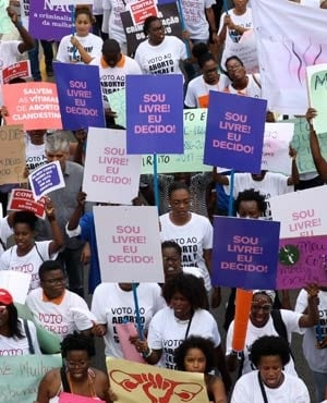 Hundreds of Angolans hold placards and shout slogans as they march to protest against a draft law that would criminalise all in Luanda, Angola. (AFP)