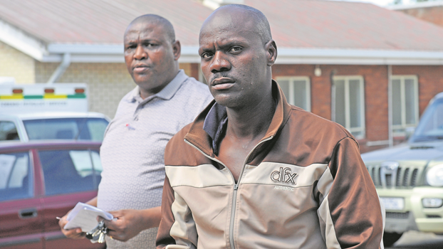 Detective Warrant Officer Sikhumbuzo Mdunge walks murder accused in the Solik case, Xolani Brian 'Maja' Ndlovu, to the cells after he appeared at the Howick Magistrate's court on Monday