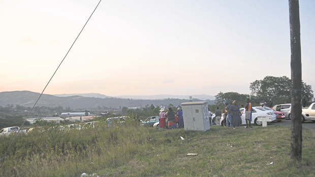 Cars and members of the public on the stretch of land that has been invaded by land grabbers in Grange