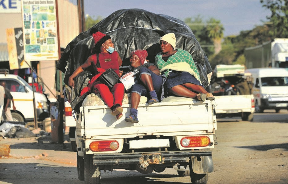 It's a struggle: Women sit precariously on the back of a bakkie packed with food in Musina, Limpopo. Picture: Leon Sadiki/City Press