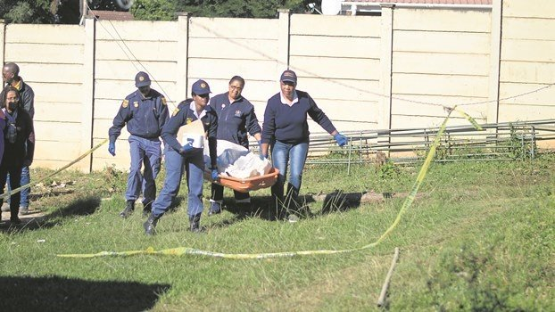 Police remove the body of a man who tried to rob a home in Scottsville. The man was attacked and killed by the family's two dogs before he could enter the house.