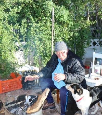 """Só moes Martin """"Duif"""" van As in die voorste erf van sy huis in Klein Voortrekkerstraat, Beaufort-Wes """"plak"""" omdat die huurder nie wou uittrek nie. By hom by die vuurtjie is sy honde Stompie (links) en Jack (regs). Foto: Francois van Niekerk"""