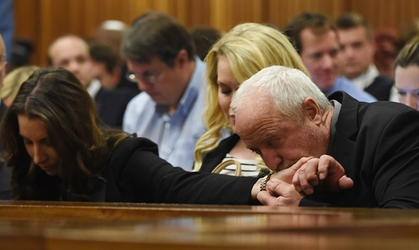 Paralympian Oscar Pistorius's father Henke Pistorius kisses the hand of his daughter Aimee Pistorius while judgment is handed down at the High Court in Pretoria on Thursday, 11 September 2014. Picture: Phill Magakoe/Independent Newspapers/ Pool